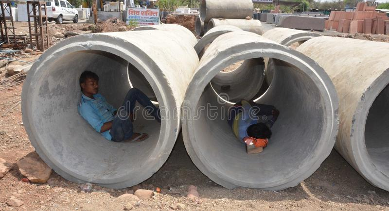 World may day. Construction Labour sleep in a concrete pipe in a very hot day in Bhopal, India stock images