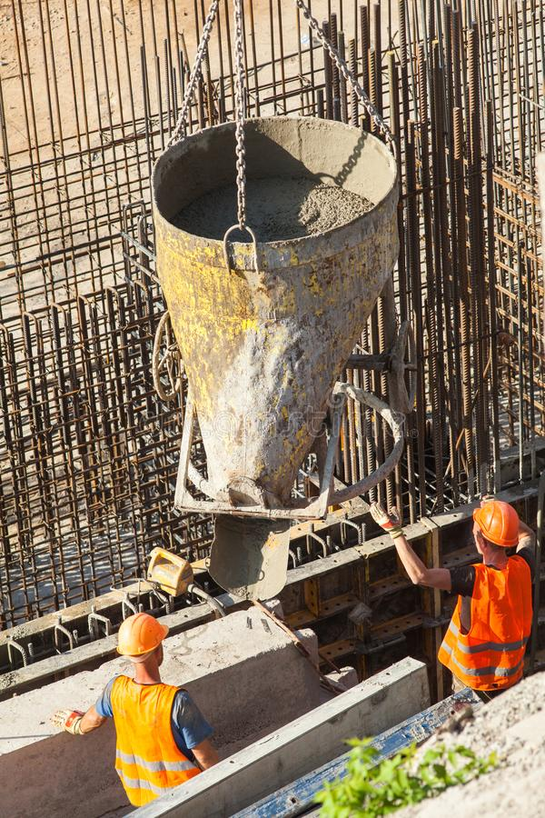 Construction of a large commercial building. Two construction workers ready fill formwork by cement and concrete stock images