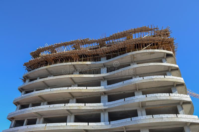 Construction of a large hotel. Bottom view. Skeleton and forest against the blue sky. royalty free stock photography