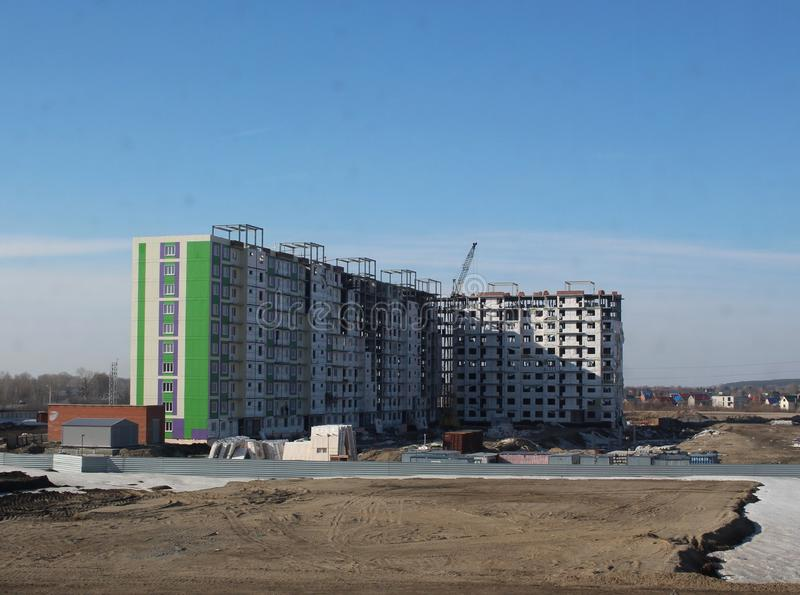 Construction of a large multi-storey building in a new residential quarter in the city near the old wooden houses in Novosibirsk. Construction of a large multi royalty free stock image
