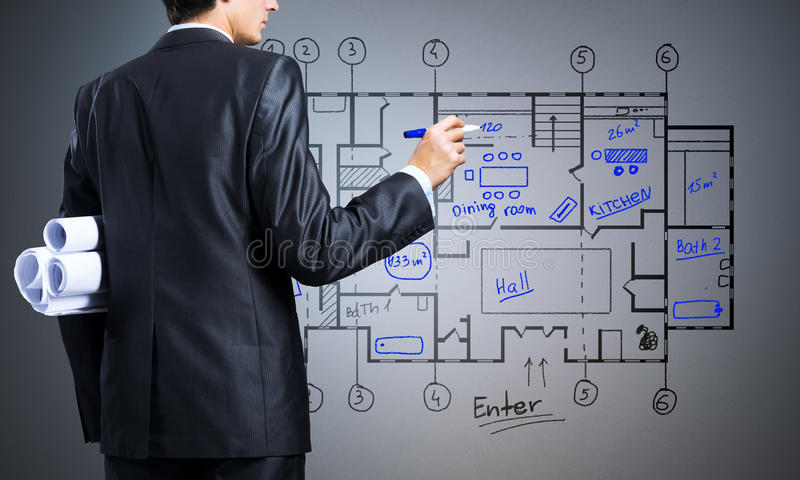 Construction layout. Young man engineer drawing building plan on screen royalty free stock image