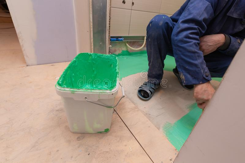 Construction level on the foreground and worker is working with palette-knife for flattening of spackling compound in royalty free stock images