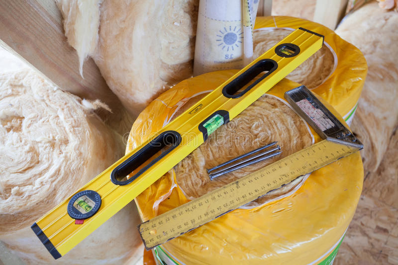 Construction level with square triangle on fiberglass insulation material. Construction level with square triangle on fiberglass insulation material stock image