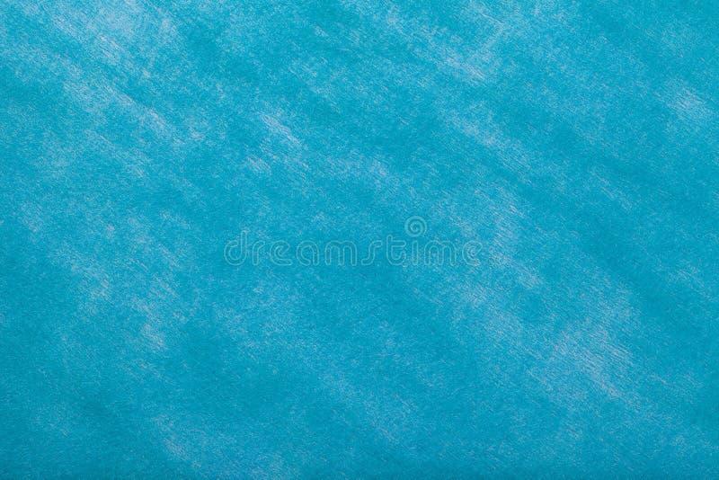 Construction of a light blue background with white spots of felt fabric, closeup. Texture of woolen matt textile. Cloth backdrop.  stock photography