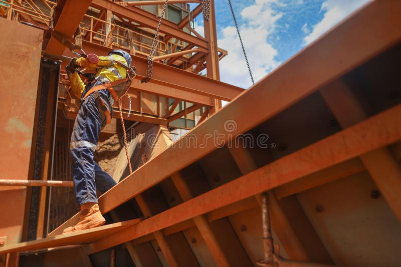 Construction maintenance worker wearing safety helmet, fall arrest harness clipping while working at height royalty free stock photo