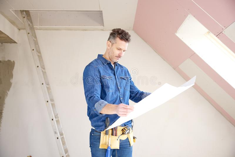 Construction man holding blueprint in his hand and working royalty free stock image