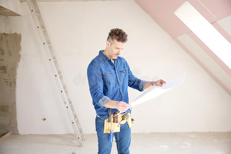 Construction man holding blueprint in his hand and working royalty free stock photos