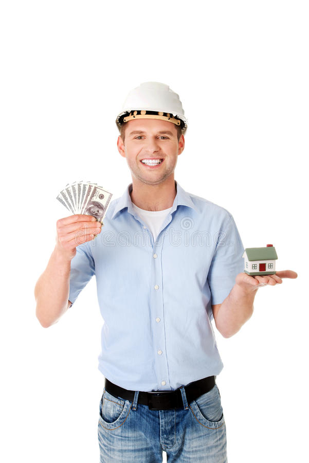 Construction man holding house model and money.  stock photos