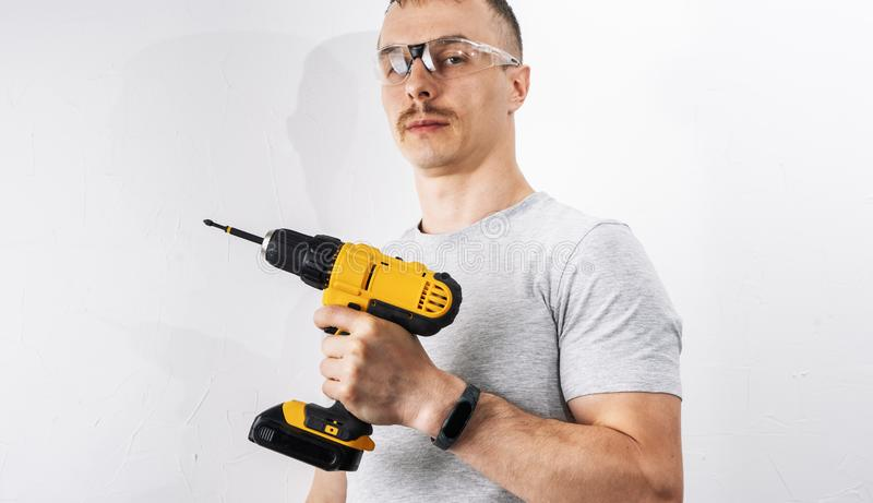 Construction: A man in protective glasses is holding a yellow electric screwdriver. stock photography