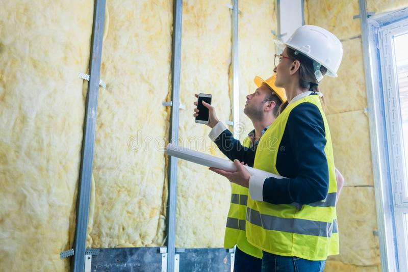 Construction manager and architect checking the insulation works royalty free stock image