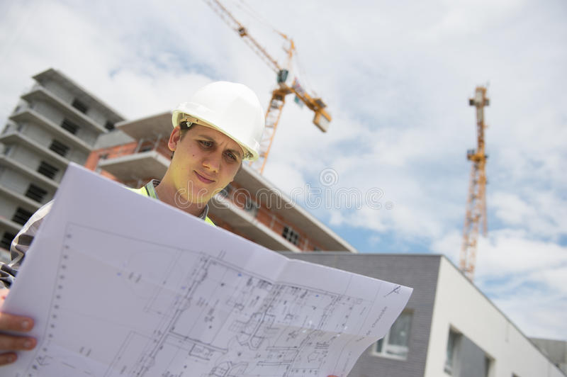 Construction manager checking building project on site. Construction manager checking construction building project on site royalty free stock image