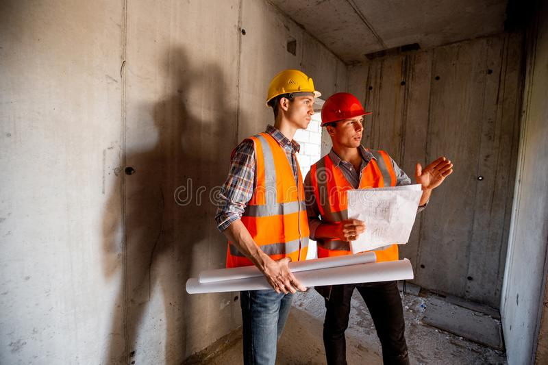 Construction manager and engineer dressed in orange work vests and helmets work with construction documentation inside. The building under construction royalty free stock photography