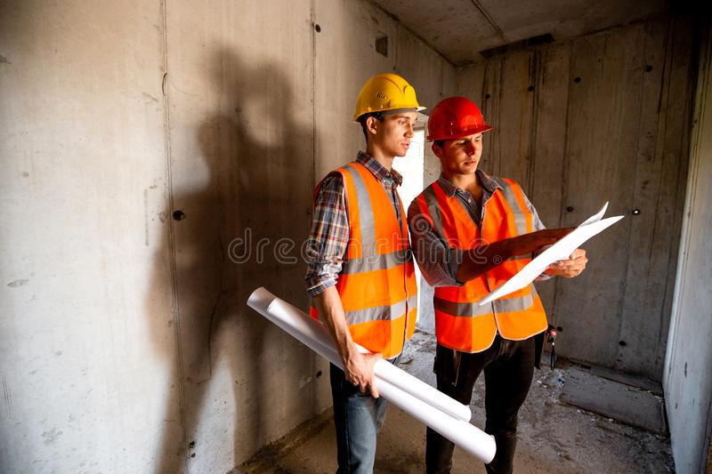Construction manager and engineer dressed in orange work vests and helmets work with construction documentation inside. The building under construction stock image