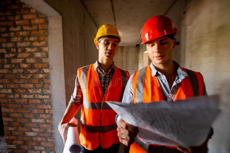 Construction manager and engineer dressed in orange work vests and helmets work with construction documentation inside. The building under construction stock photo