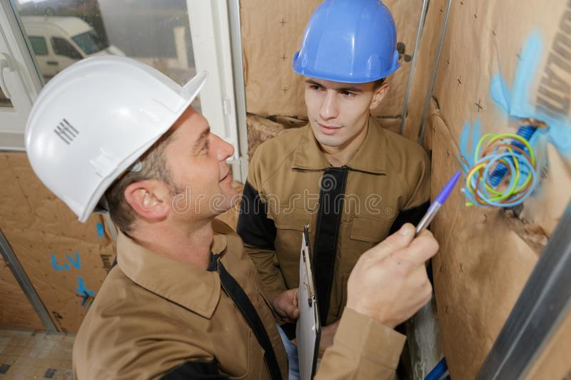 Construction manager pointing at wires showing up royalty free stock image