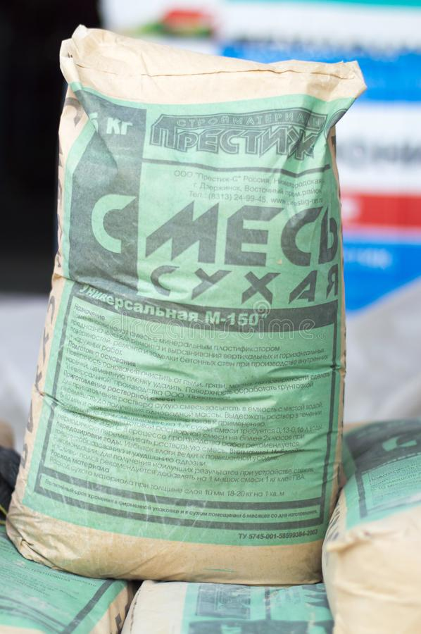 The construction market in the open air. Dry building mortar in a bag of 25 kg. put up for sale. Nizhny Novgorod, Russia August 30, 2017: The construction stock image