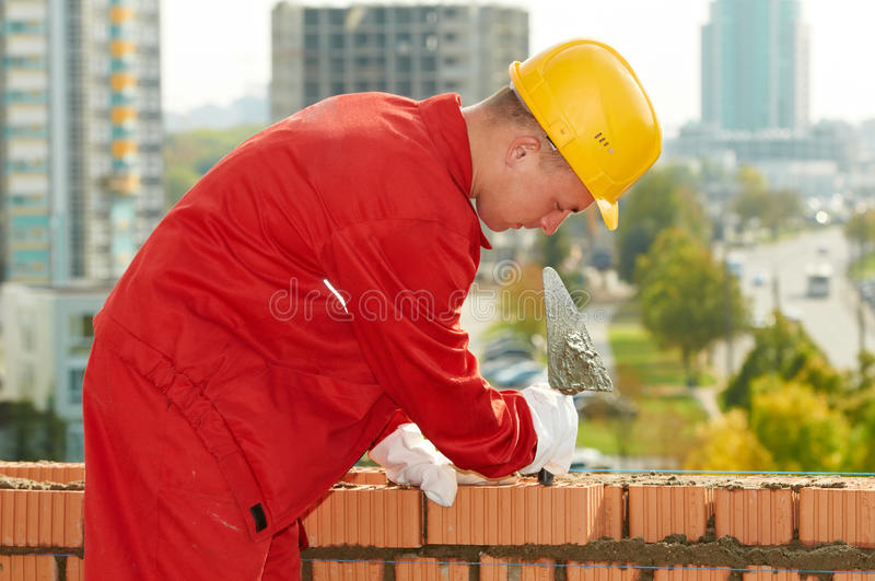 Construction mason worker bricklayer. Making a brickwork with trowel and cemant mortar royalty free stock photos