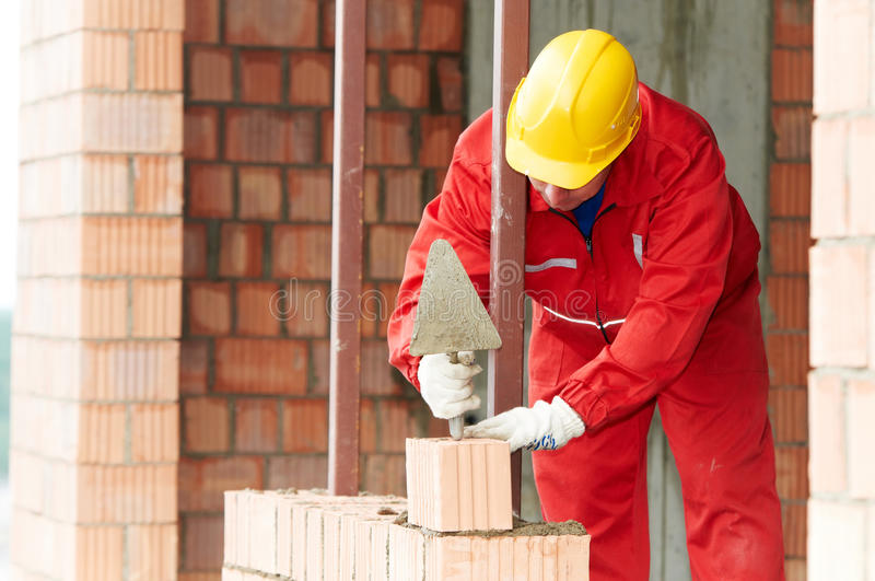 Construction mason worker bricklayer. Making a brickwork with trowel and cemant mortar stock photos