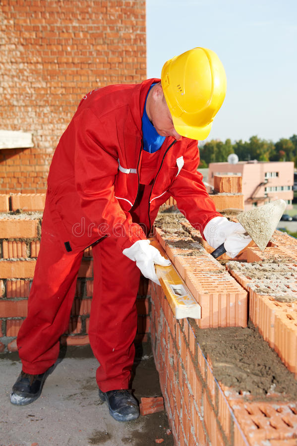 Construction mason worker bricklayer. Making a brickwork with trowel and cemant mortar royalty free stock photography