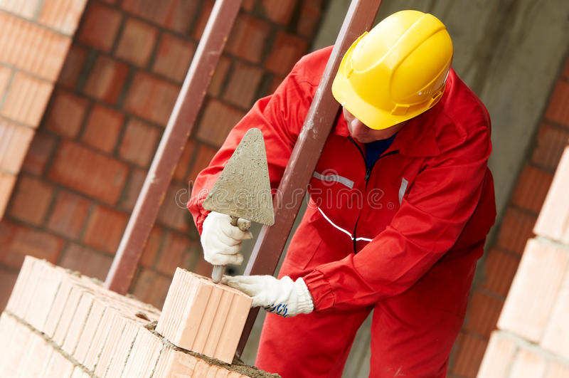 Construction mason worker bricklayer. Making a brickwork with trowel and cemant mortar stock images