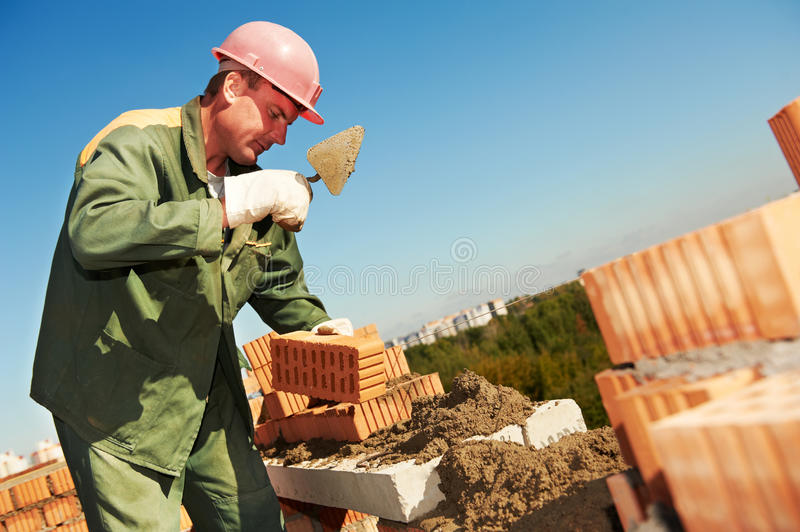 Construction mason worker bricklayer. Making a brickwork with trowel and cemant mortar stock photo