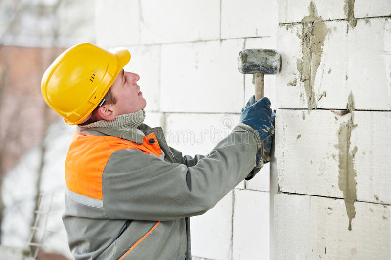 Construction mason worker bricklayer. Installing calcium silicate brick by hammer hitting work royalty free stock image