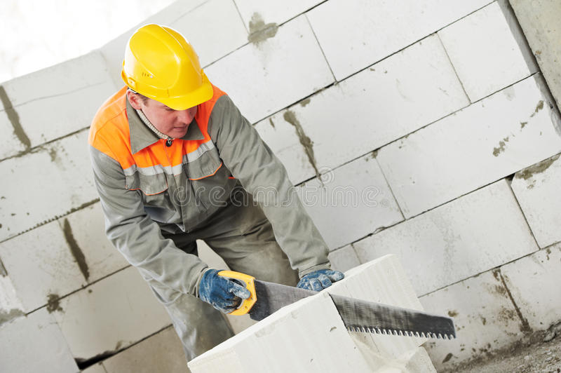 Construction mason worker bricklayer. Sawing off a calcium silicate lime sand brick stock images