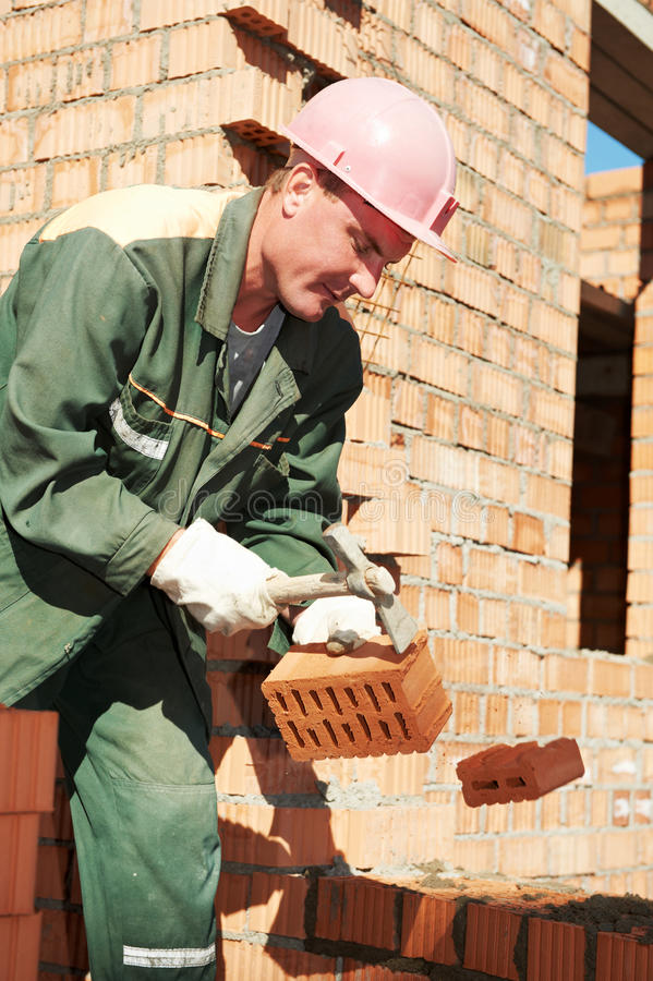 Construction mason worker bricklayer. Making a brickwork with trowel and cemant mortar stock photography