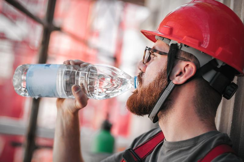 Construction mason worker on scaffolding, resting and drinking water. Construction mason worker sitting high on the scaffolding, resting and drinking water royalty free stock image