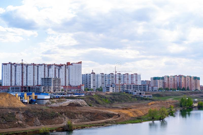 Construction of a new multi-storey building on the river Bank. Construction of a multi-storey building with cranes in the area of new buildings near the river stock images