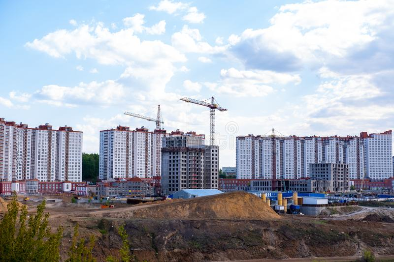 Construction of a new multi-storey building on the river Bank. Construction of a multi-storey building with cranes in the area of new buildings near the river stock photography