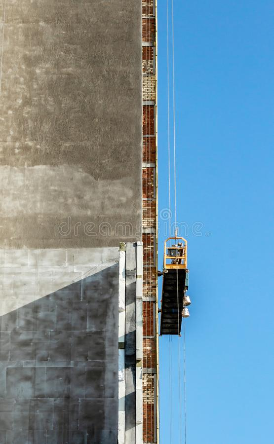 Construction of a multi-storey building, an external front elevator without people moving along the facade, the concept of frozen. Construction, against the stock photos