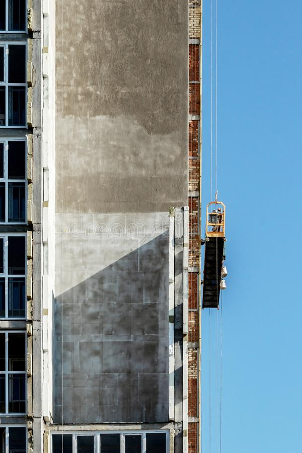 Construction of a multi-storey building, an external front elevator without people moving along the facade, the concept of frozen. Construction, against the stock photography