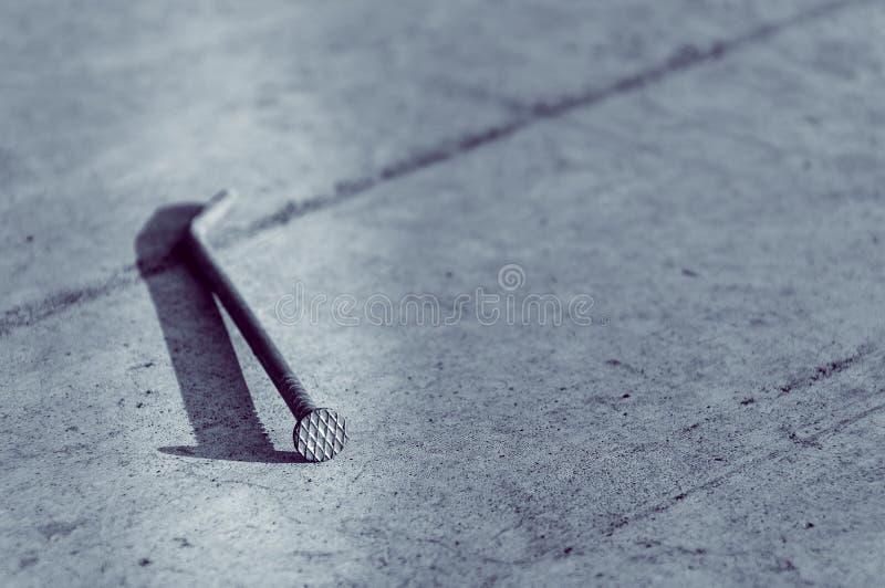 Construction nail. A large nail lies on a concrete base stock photo