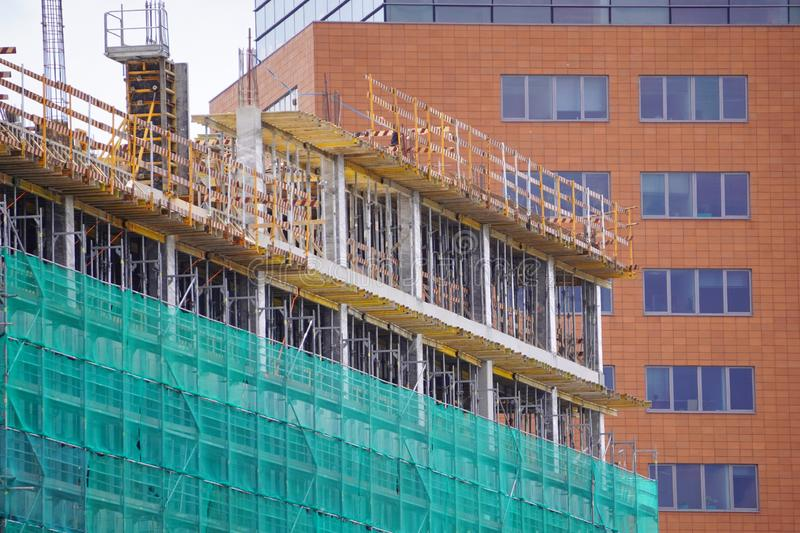 Construction of a new building made of metal-concrete and brick on the background of the built house. modern technologies in royalty free stock photography