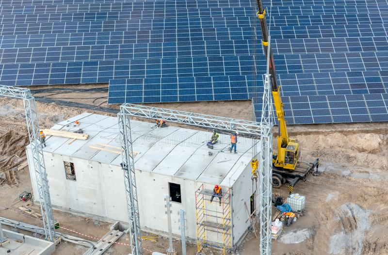 Construction of a new electrical substation and a building for high-voltage equipment. On the background of solar panels - a top view stock images