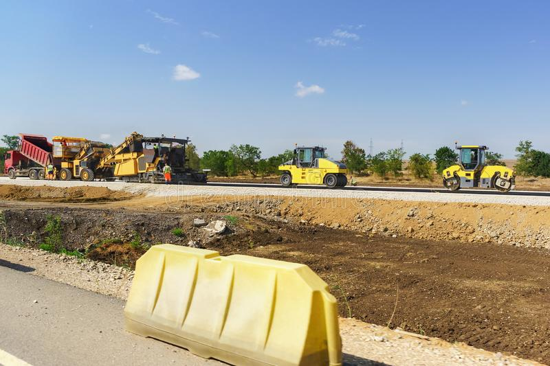 Construction of a new highway Tavrida in the Crimea. Yellow rollers and pavers. Sunny day stock photography