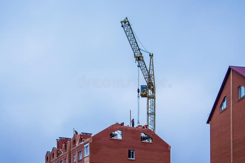 Construction of a new house, builders working on the top of the royalty free stock photo