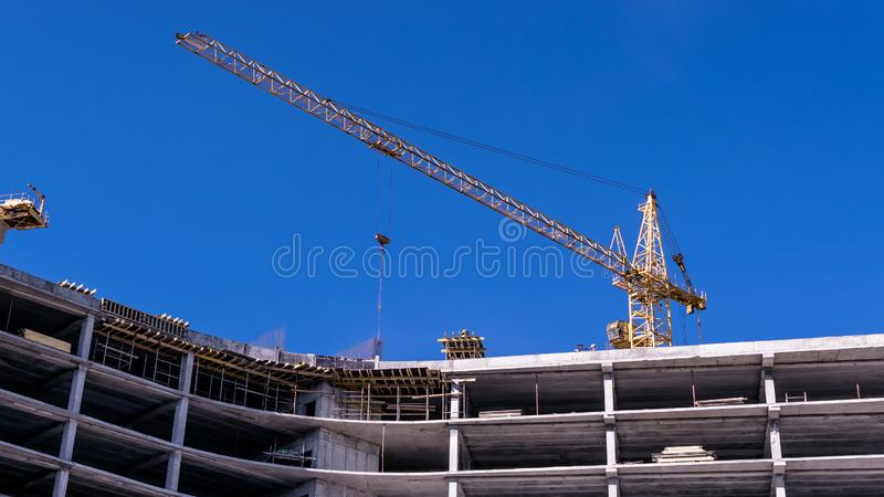 Construction of a new house in the way of monolithic con crete pouring using a crane. Construction of a new house in the way of monolithic concrete pouring using stock photo