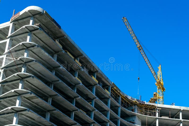 Construction of a new house in the way of monolithic con crete pouring using a crane. Construction of a new house in the way of monolithic concrete pouring using royalty free stock image