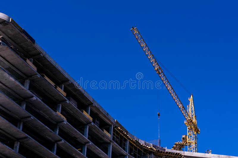Construction of a new house in the way of monolithic con crete pouring using a crane. Construction of a new house in the way of monolithic concrete pouring using royalty free stock photo