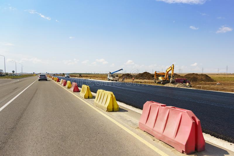 Construction of a new modern highway Tavrida in the Crimea. Fresh black asphalt is separated by yellow and red road barriers. royalty free stock photography