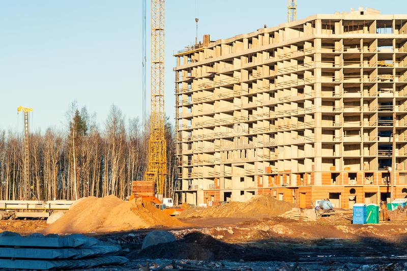 Construction of a new multi-storey building surrounded by forests. Construction cranes against the blue sky royalty free stock photos
