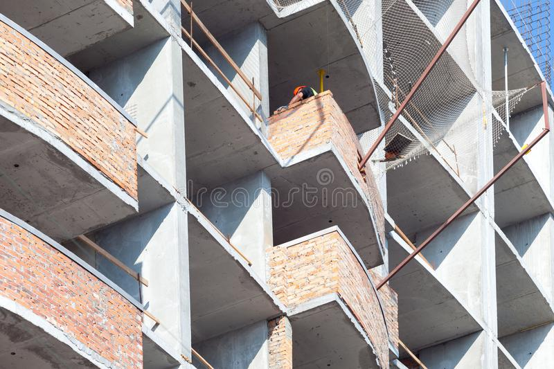 Construction of a new multi-storey building. Worker laying bricks to make a wall on the balcony, he is putting grout on top of a b royalty free stock photo