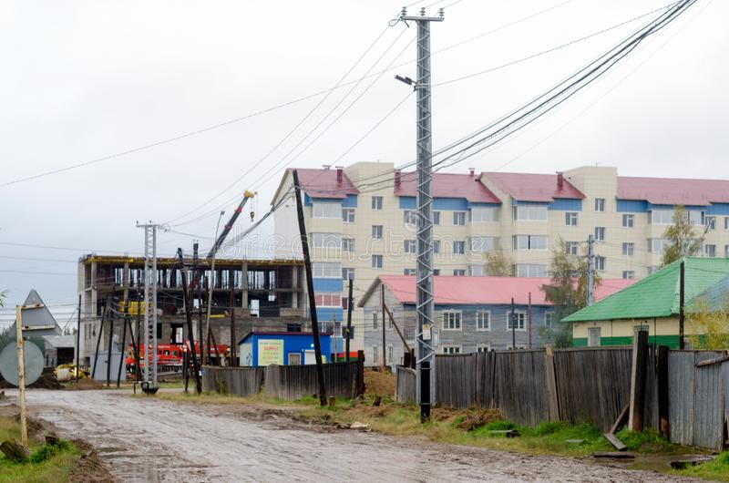 The construction of a new multistory building in the North in the village of Yakutia, Suntar at the end of the wet street. With a fence of old railway cottages stock photography