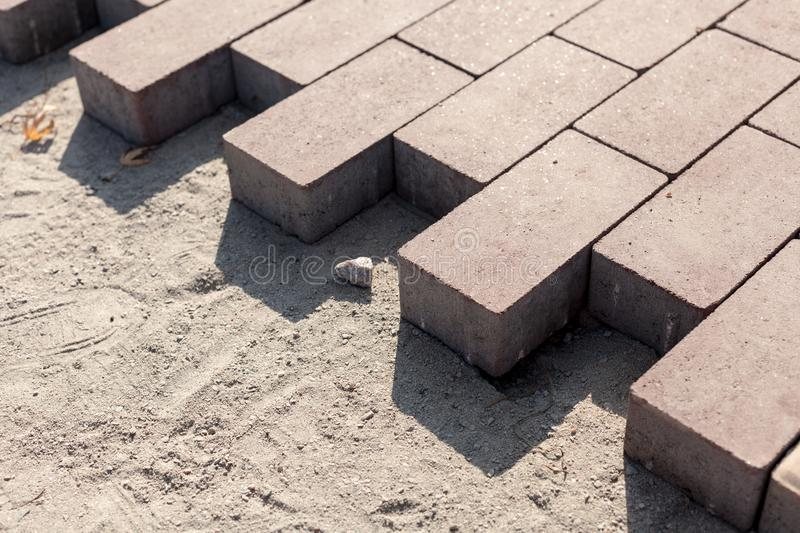 Construction of a new pavement of paving slabs closeup detail. Pavement cobblestone blocks construction of path, road or sidewalk. royalty free stock images