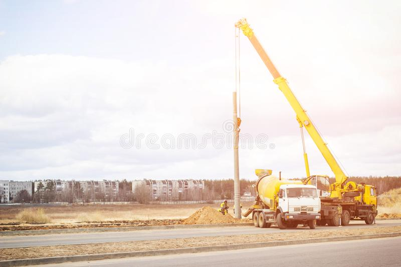 Construction of a new road and installation of lampposts using a truck crane and cement truck, workers, copy space, profession. Construction of a new road and stock photos