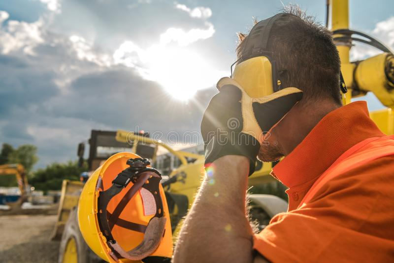 Construction Noise Reduction. Construction Noise. Heavy Machinery Operator with Noise Reduction Headphones on His Head. Industrial Concept royalty free stock photo