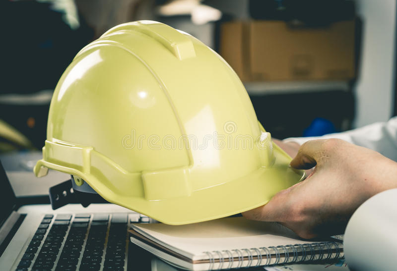 Construction office worker holding Yellow Helmet royalty free stock image