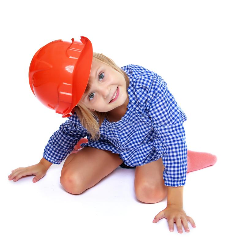 Little girl in the construction helmet. stock photo
